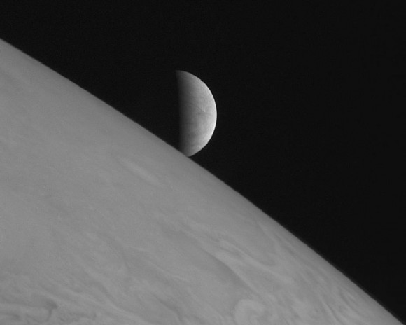 Europa rising above Jupiter's cloudtops, as captured by the New Horizons spacecraft - en route to Pluto - in 2007.  Image via NASA.