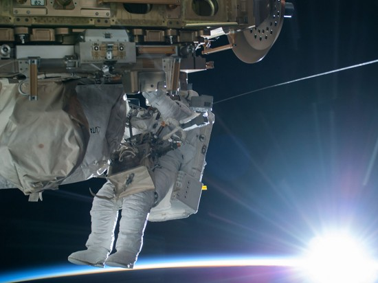 NASA astronaut Terry Virts Flight Engineer of Expedition 42 on the International Space Station is seen working to complete a cable routing task while the sun begins to peak over the Earth's horizon on February 21 2015. Image credit: NASA