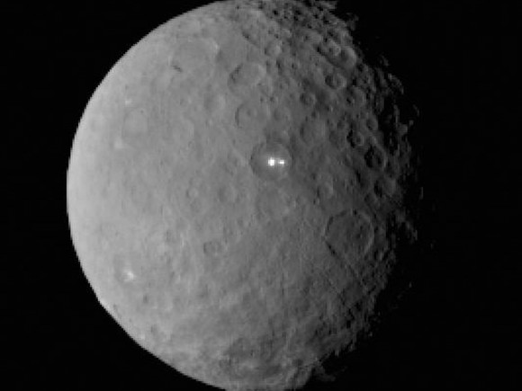 Cratered round, gray small planet with bright white spots in a large crater.