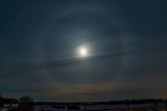 Bright moon with halo and wispy clouds and one starlike dot outside halo.