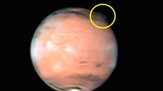 Observations of a mysterious plume-like feature (marked with yellow arrow) at the limb of the Red Planet on 20 March 2012. The observation was made by astronomer W. Jaeschke. The image is shown with the north pole towards the bottom and the south pole to the top.