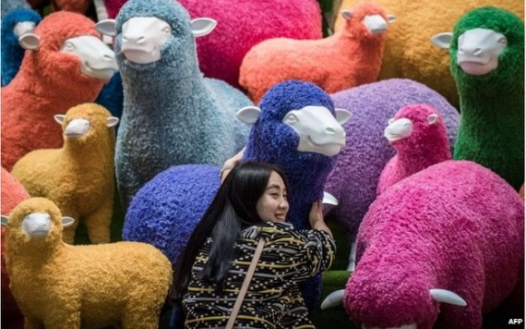 A woman poses with a sheep display in Hong Kong, which like many cities has put up colorful lunar New Year's decorations.  Image via Agence France-Presse.