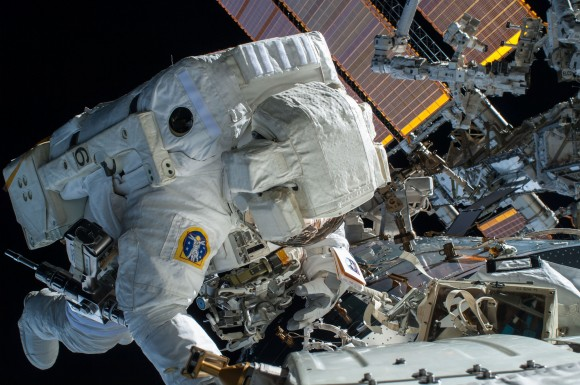 NASA astronaut Terry, Virts Flight Engineer of Expedition 42 is seen working to complete a cable routing task while near the forward facing port of the Harmony module on the International Space Station. February 21, 2015. Image credit: NASA