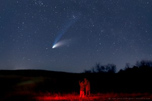 Two people in a field looking at a comet.