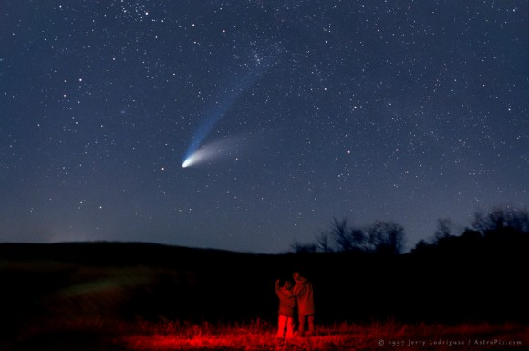Two people looking at a bright smudge with two long, glowing, fuzzy tails in a starry night sky.