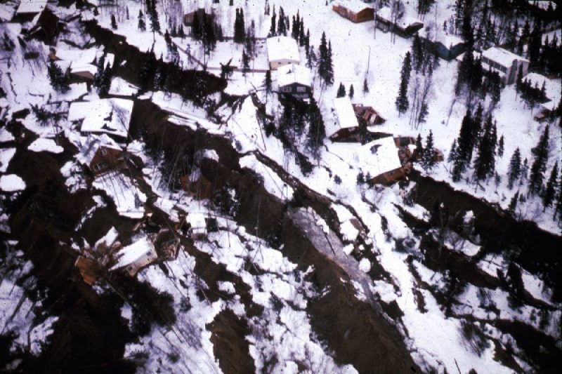 Aerial view of houses and trees tumbled down a long hillside with many large, deep cracks.