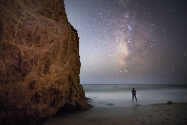 A man on a beach, next to a tall rocky cliff, under the Milky Way.