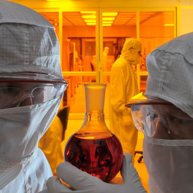 Professor Dean Neikirk (left) and Sean Murphy examine a stable dispersion of nanoparticles in the cleanroom at the Microelectronics Research Center on the Pickle Research Campus, University of Texas.  Nanotechnology research at universities around the world will revolutionize oil and gas exploration and production, solar harvesting, and power grid storage and transmission.  Photo by David Stephens, Bureau of Economic Geology, Univ. of Texas.