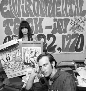 Man and woman in front of Environmental Teach-In poster with groovy 1960s style lettering.