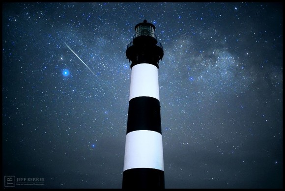 Striped lighthouse seen from base with starfield and white streak in sky.