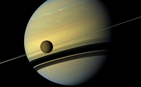 A giant of a moon appears before a giant of a planet undergoing seasonal changes in this natural color view of Titan and Saturn from NASA's Cassini spacecraft. Image Credit: NASA/JPL-Caltech/SSI