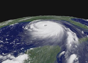 Large round white hurricane seen above from the side, with distinct spirals and eye, in Gulf of Mexico with green land areas visible.