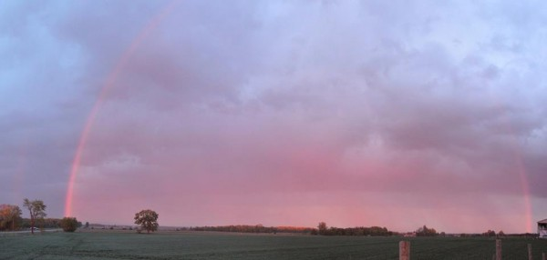 Partial arc of pink in pink and blue twilight clouds.