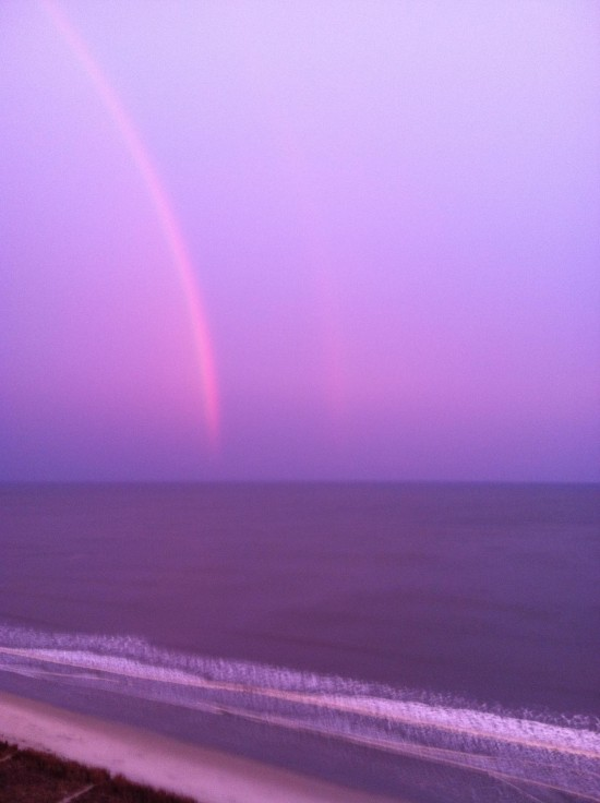 Partial pink semicircles in deep blue sky above purple sea.