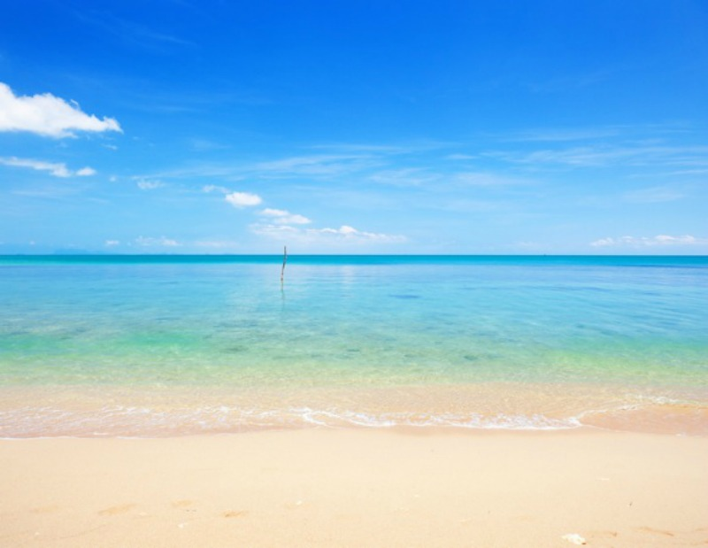 Pale tan beach, green to blue calm sea, blue sky deepening in color toward the top, a few white clouds.