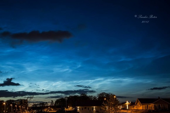 Noctilucent clouds on horizon under cloudy sky, lighted town below.