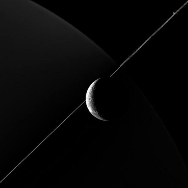 NASA's Cassini imaging scientists processed this view of Saturn's moon Dione, taken during a close flyby on June 16, 2015. This was Cassini's fourth targeted flyby of Dione and had a close approach altitude of 321 miles (516 kilometers) from Dione's surface. Also making an appearance in this image is Saturn's geysering moon Enceladus, seen in the upper right, just above the bright line of Saturn's rings. Credit: NASA/JPL-Caltech/Space Science Institute