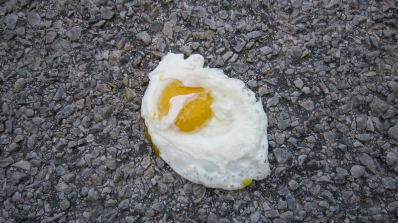 Fried egg, yellow yolk in middle of oval white, lying on the grainy black surface of asphalt.