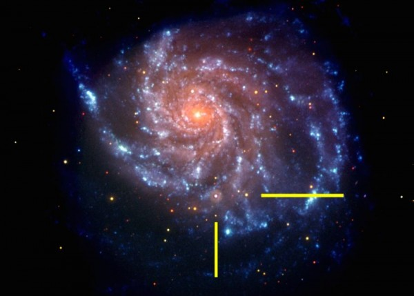 Galaxy M101, one of billions of galaxies in our universe.  The bars show the location of a supernova.  Image via NASA/Swift.