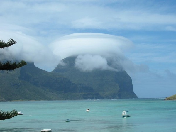 Thick lenticular cloud like a cap on a steep island mountain, sea in foreground.