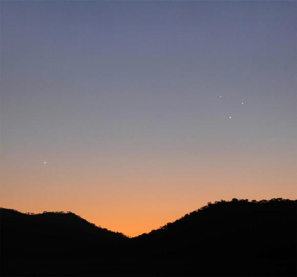 View larger. Evening dusk on August 7, 2015: Venus is off by herself to the left. The triangle of lights to the right: Regulus (brightest star in the constellation Leo) at top, Jupiter at bottom and Mercury in between.