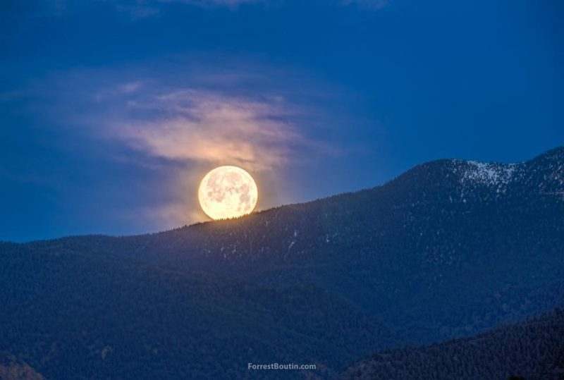 Bright full moon ascending behind a mountain ridgeline.