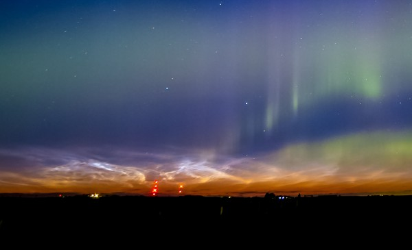 Thin shining clouds on horizon with glowing vertical curtain of aurora on right.