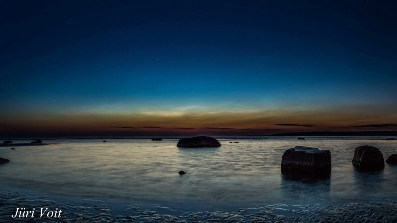 Noctilucent clouds in deep blue sky over twilit sunset, seashore with large rocks.