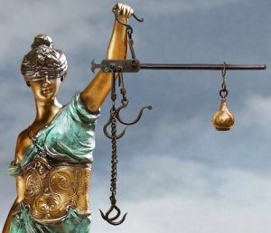 Blindfolded statue holding scales with hooks on short end and weight on long end.