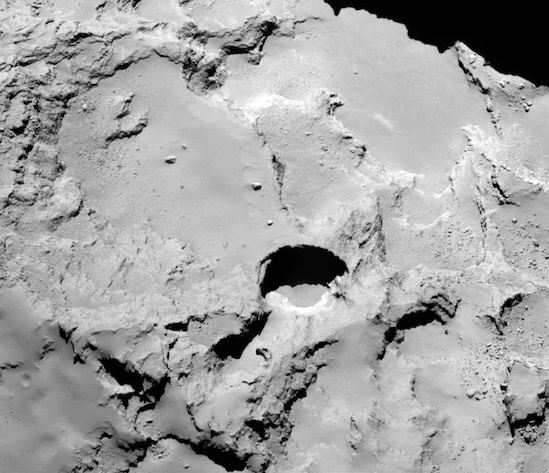 This close-up image shows the most active pit, known as Seth_01, observed on the surface of comet 67P/Churyumov-Gerasimenko by the Rosetta spacecraft. A new study suggests that this pit and others like it could be sinkholes, formed by a surface collapse process similar to the way these features form on Earth. Image via Vincent et al., Nature Publishing Group