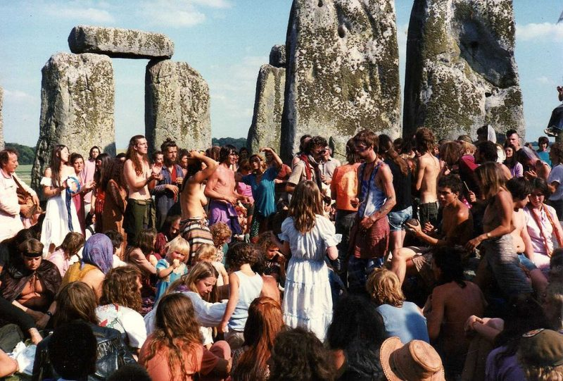 Crowd of mostly young people, somewhat hippie looking, among enormous rough-cut standing stones.