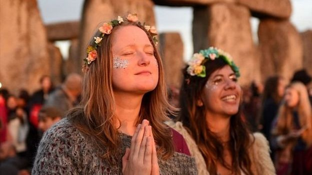 Ecstatic young women with flowers in their hair, one with her eyes closed, Stonehenge in background.