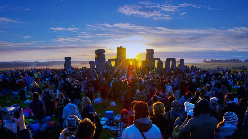 Big crowd in front of huge rough-cut standing stones with sun rising behind them.