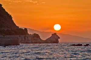 Rocky shoreline, the sun a yellow-white circle above large pointy rock against orange sky.