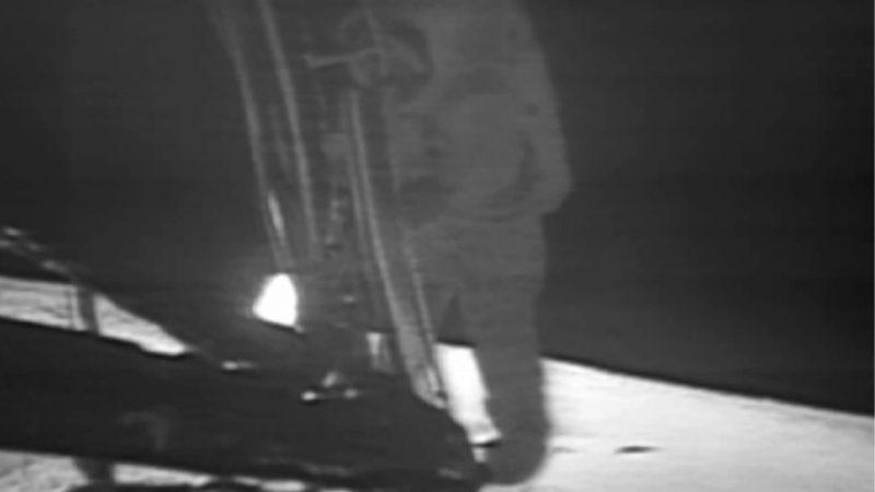 Fuzzy black & white photo of astronaut stepping off ladder of lunar lander.