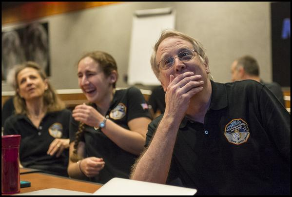 Three New Horizons team members react with joy and amazement.