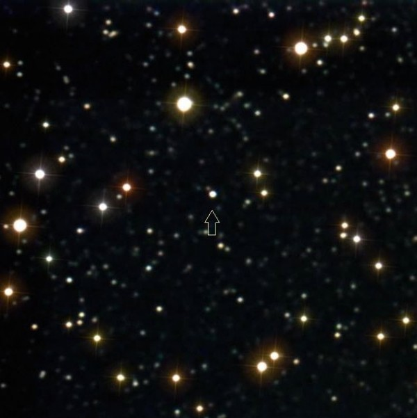 Scattered bright dots of stars with one small dot marked, the planet Pluto.