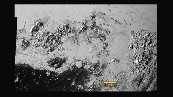 View larger. | Unlabeled image of Pluto plains, mountains, craters, and flowing nitrogen ice.