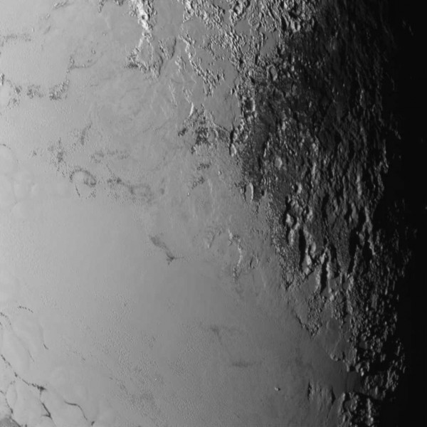 View larger. | New Horizons spacecraft using the LORRI (LOng Range Reconnaissance Imager) camera. Image showing a large area near Pluto's sunset terminator, reveals how frozen nitrogen has flowed out from the plains into old, more cratered terrain. The nitrogen ice has flowed like normal water ice does on Earth, even in Earth's coldest places in Greenland and Antarctica. This surface is so cold, it has actual Nitrogen Ice glaciers. On Pluto however, water ice is as hard as solid rock and would not flow at those temperatures, but nitrogen ice does flow over time at the average surface temperatures on Pluto of minus 232 Celsius / minus 386 Fahrenheit or 41 Kelvin.