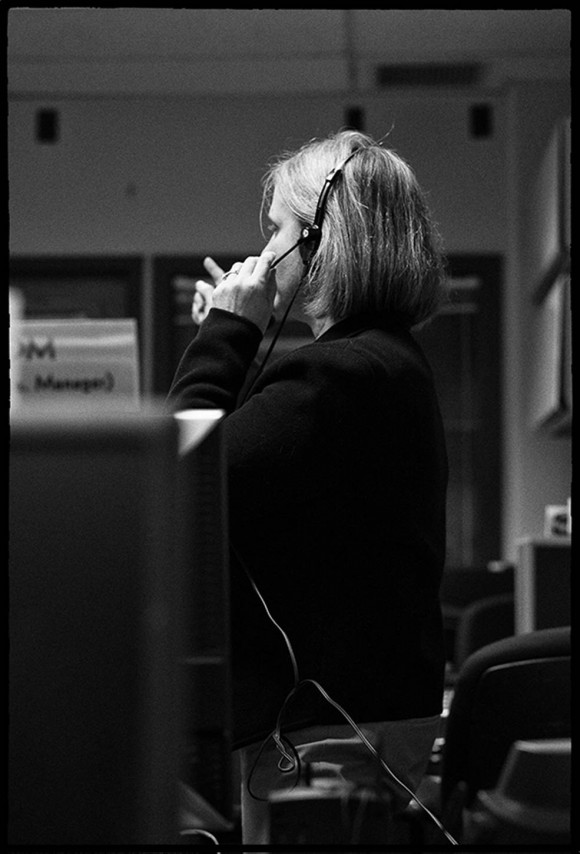 """Alice Bowman, the Mission Operations Manager, at work in the Mission Operations Center. On the job, Bowman is the """"MOM"""" of the MOC. This photo was taken during the New Horizons (final) hibernation wake-up on December 6, 2014. Bowman said, """"It looks like I was either asking for a different configuration or asking about the telemetry I was seeing on the displays."""" Image credit: SwRI/JHUAPL"""