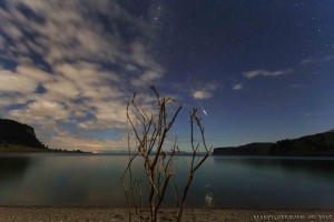 Meteor and partly cloudy sky over lake and bare branches, above Taupo supervolcano.