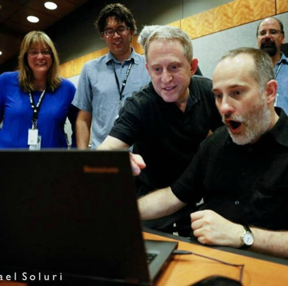 6 scientists looking at a computer screen react with amazement to the latest image of Pluto.