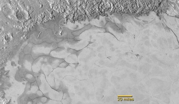 New Horizons discovers flowing ices in Pluto's heart-shaped feature. In the northern region of Pluto's Sputnik Planum (Sputnik Plain), swirl-shaped patterns of light and dark suggest that a surface layer of exotic ices has flowed around obstacles and into depressions, much like glaciers on Earth. Image via NASA/JHUAPL/SwRI