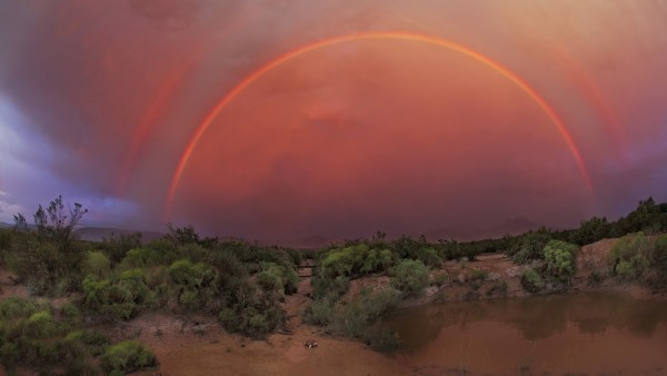 Two concentric red semicircular arcs against deep orange clouds over a brushy desert lanscape.