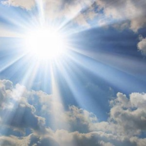 A very bright sun shining in a partly cloudy sky.