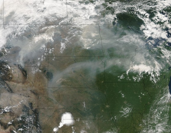 On August 21, 2015 the Aqua satellite captured this image of the smoke from the fires on the west coast of the United States wafting eastward on the jet stream.  In this image the smoke is obscuring parts of Montana, North and South Dakota, Minnesota, and Wisconsin.  Residents of these states are on notice that sunsets will be much redder and more orange as long as the smoke lingers over their area. The reason? The size of the smoke particles is just right for filtering out other colors meaning that red, pink and orange colors can be seen more vividly in the sky. Image credit: Jeff Schmaltz, MODIS Rapid Response Team.