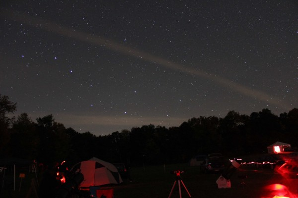 Big Dipper above where people are setting up telescopes in red light.