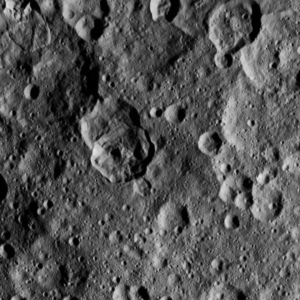 View larger. | Here is a 143-km / 89-mile-wide cratered area within the northern hemisphere on 1 Ceres. There is a nice pair of overlapping craters and to the top left what appears to be an old crater with fresher intruding frozen impact melt.