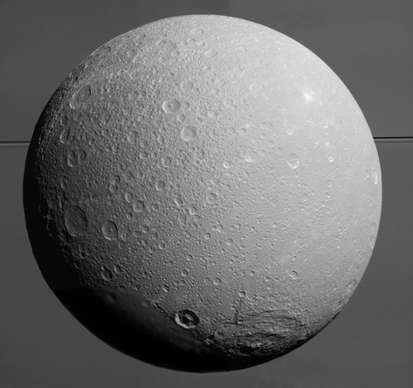This view from NASA's Cassini spacecraft looks toward Saturn's icy moon Dione, with giant Saturn and its rings in the background, just prior to the mission's final close approach to the moon on August 17, 2015. At lower right is the large, multi-ringed impact basin named Evander, which is about 220 miles (350 kilometers) wide. The canyons of Padua Chasma, features that form part of Dione's bright, wispy terrain, reach into the darkness at left. Image credit: NASA