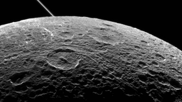 A view of Saturn's moon Dione captured by NASA's Cassini spacecraft during a close flyby on June 16, 2015. The diagonal line near upper left is the rings of Saturn, in the distance. Image credit: NASA/JPL-Caltech/Space Science Institute